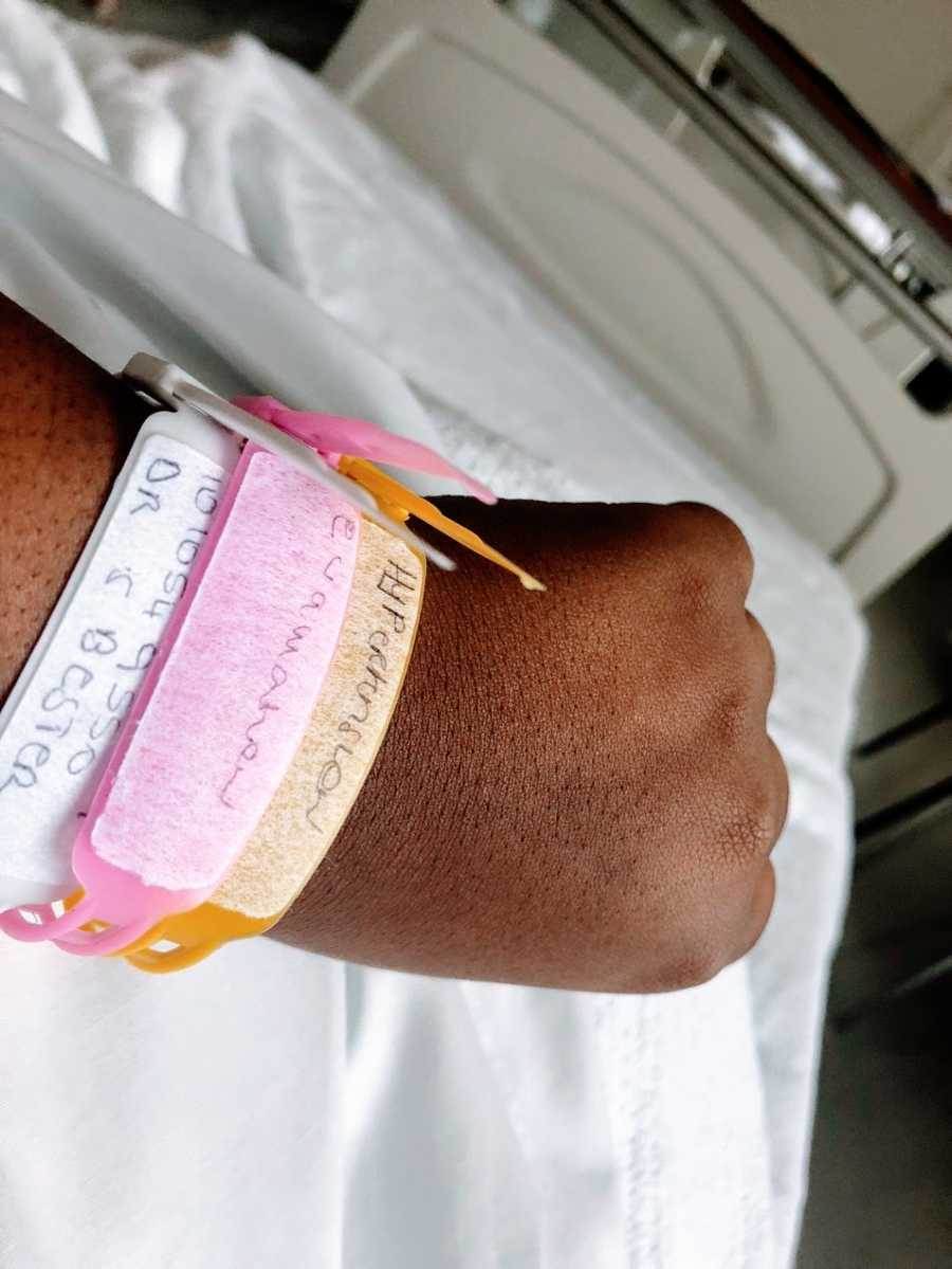 A woman in the hospital displays her hospital bracelets on her wrist