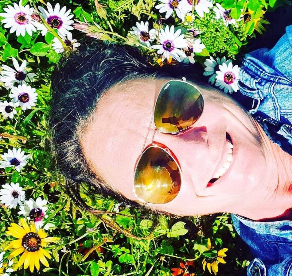 A woman lies in the grass on her back wearing sunglasses