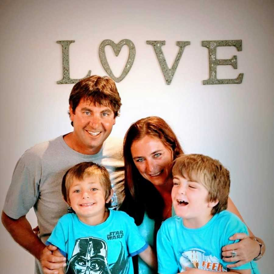 Parents stand with their two children in front of a sign that says love
