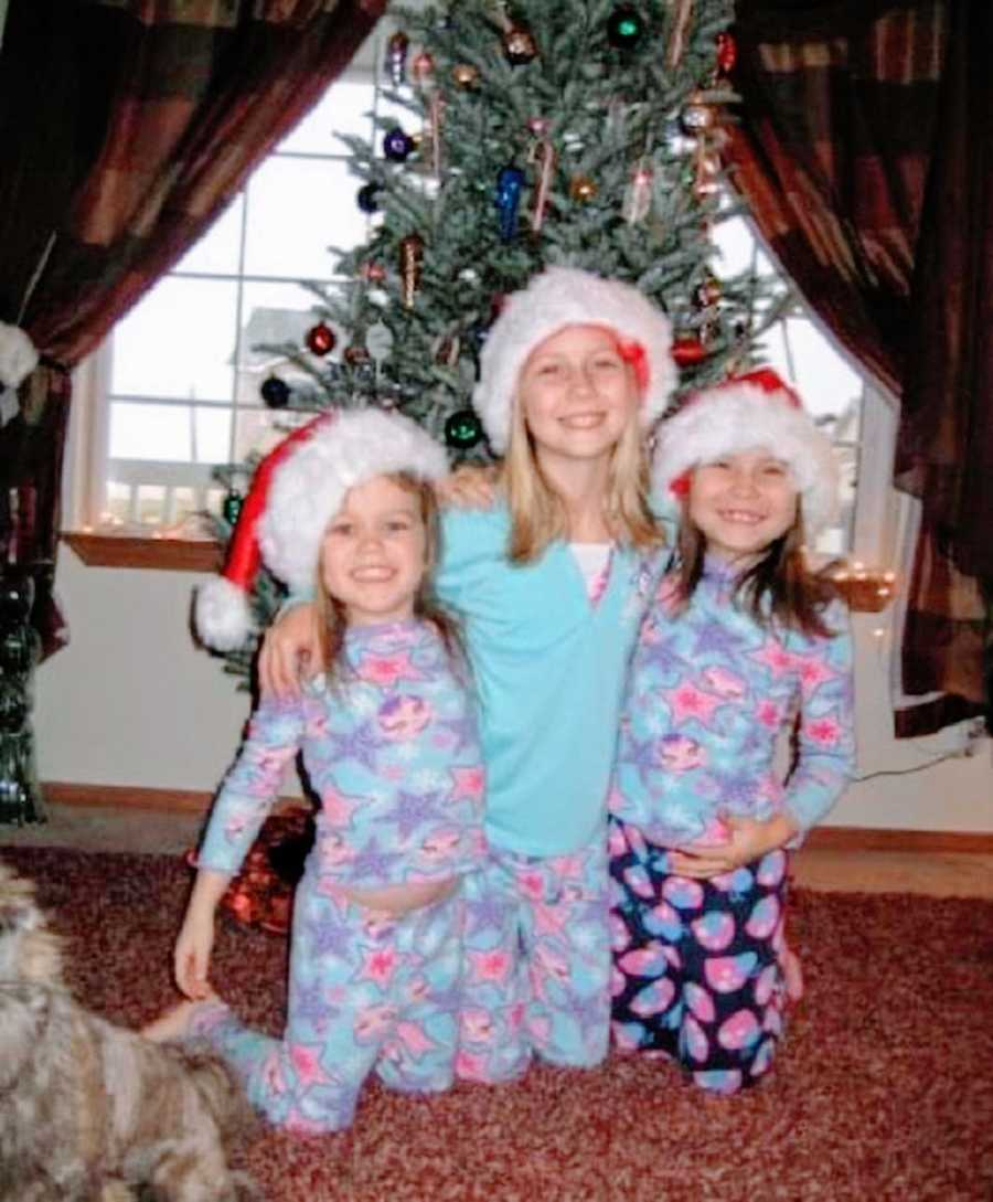 Three sisters stand together on Christmas