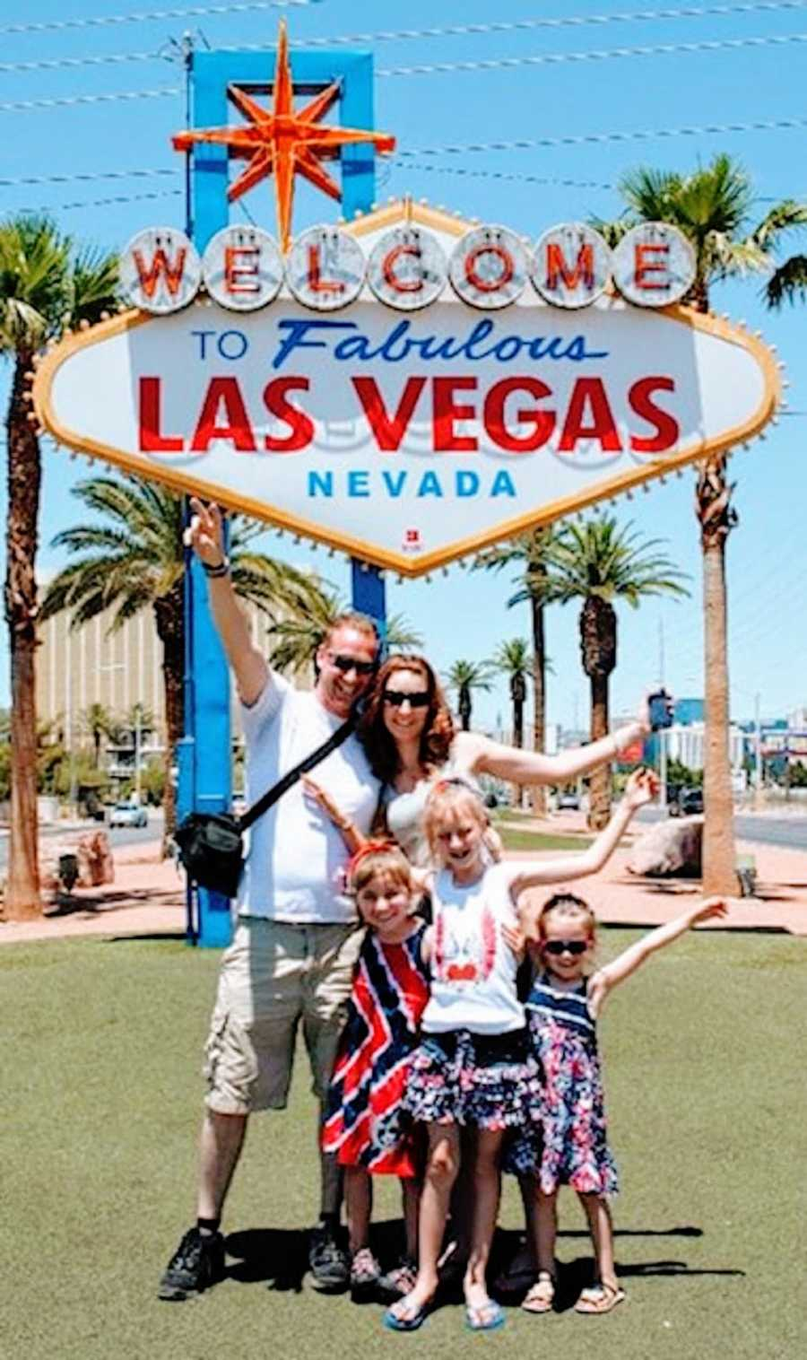 A family stand together outside of a Vegas sign