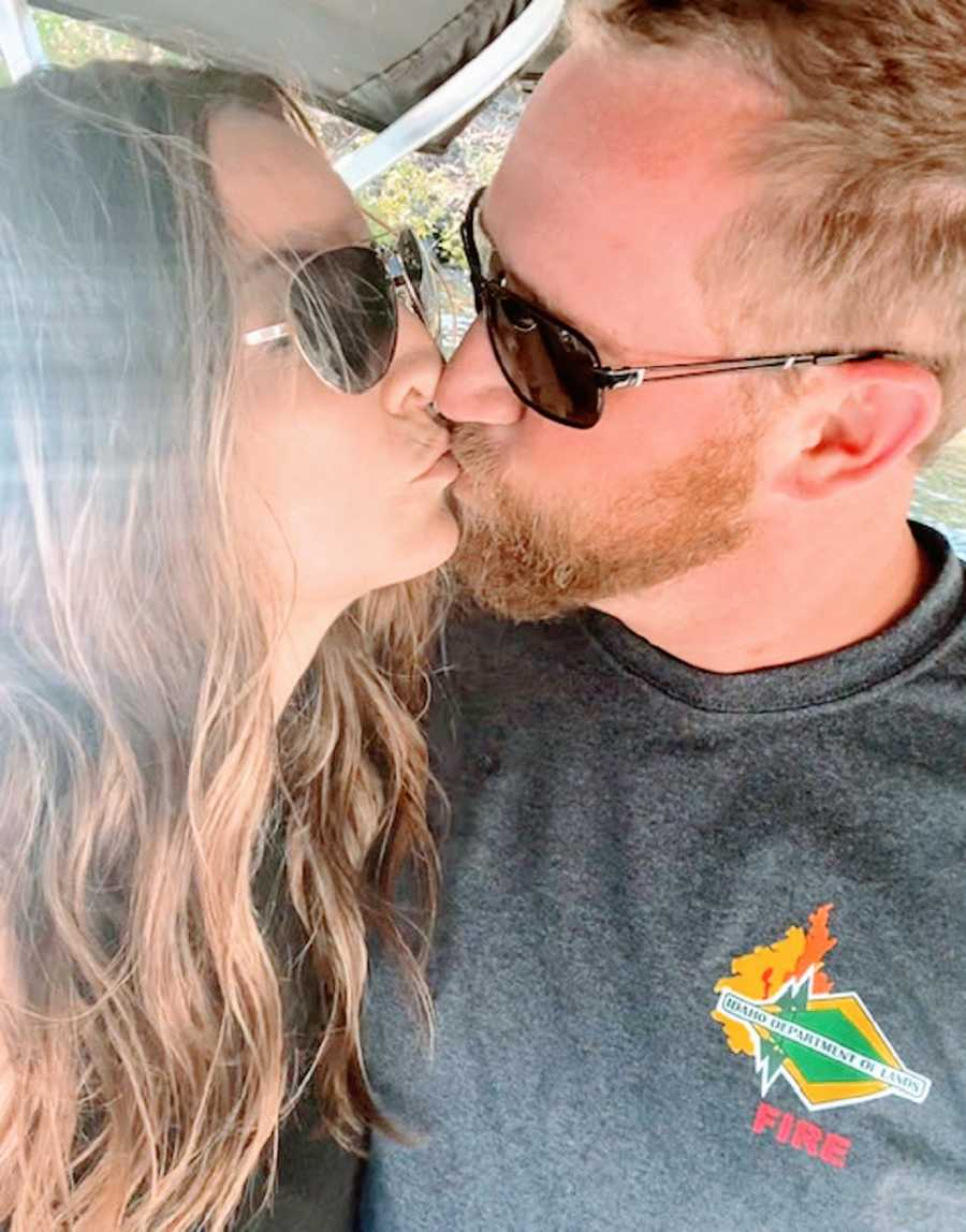 A couple kissing while wearing sunglasses