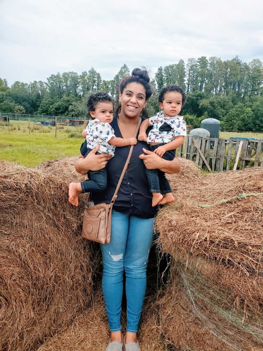 A mom holds her twin sons by a haystack