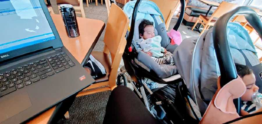 A pair of twins sleep in a stroller next to their mom's computer