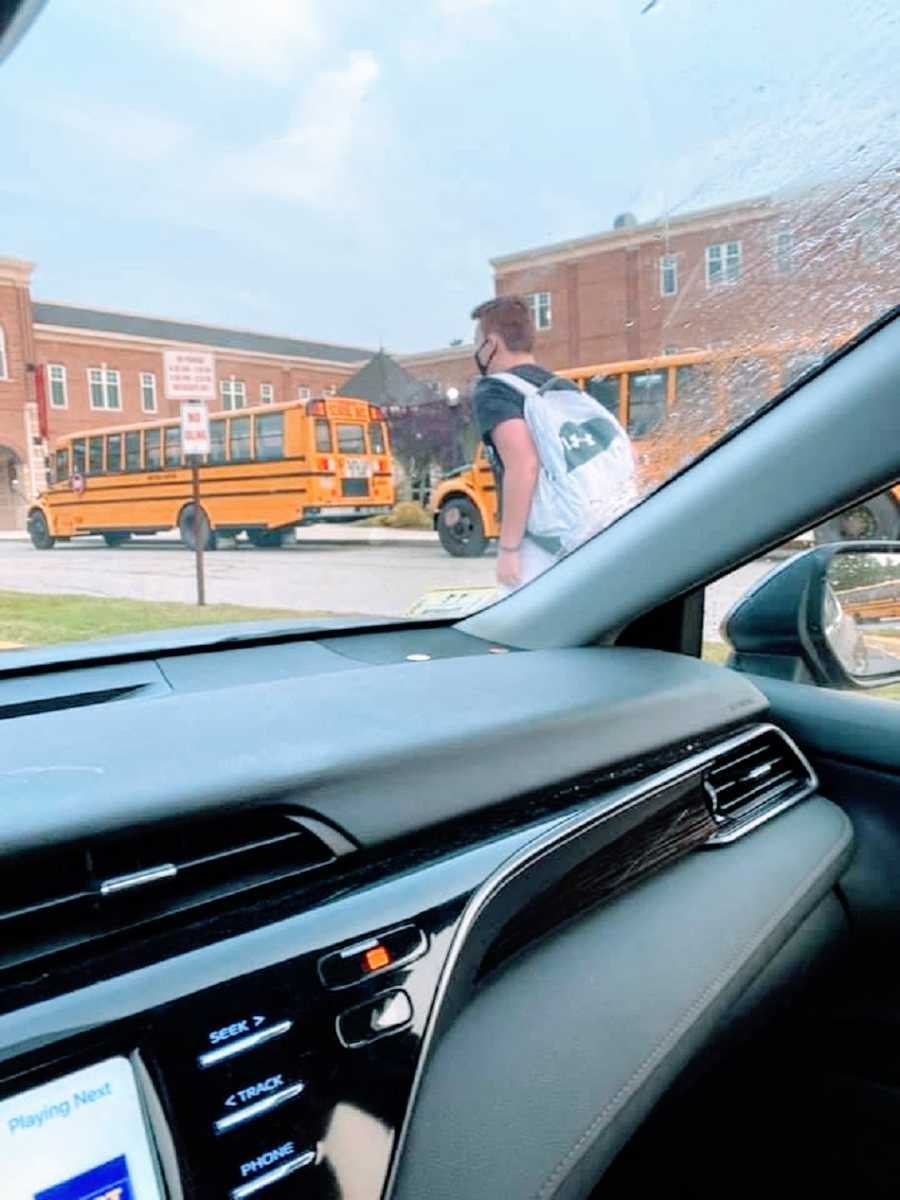 A boy returns to school wearing a mask as seen through a car window