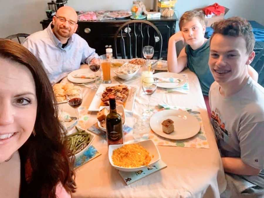A family of four sit together around a dinner table