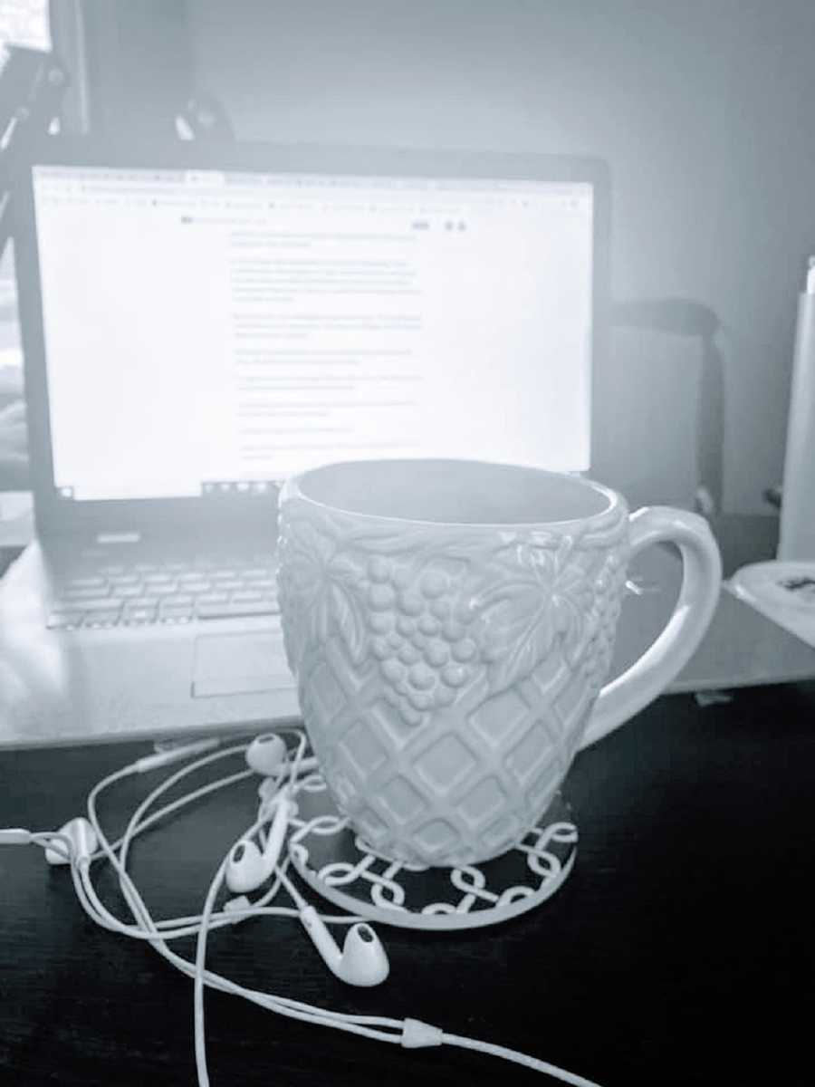 A mug and headphones sit on a desk in front of a computer