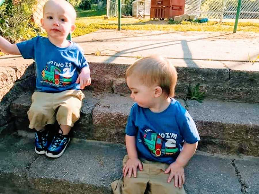 Twin boys wearing matching outfits sitting on steps
