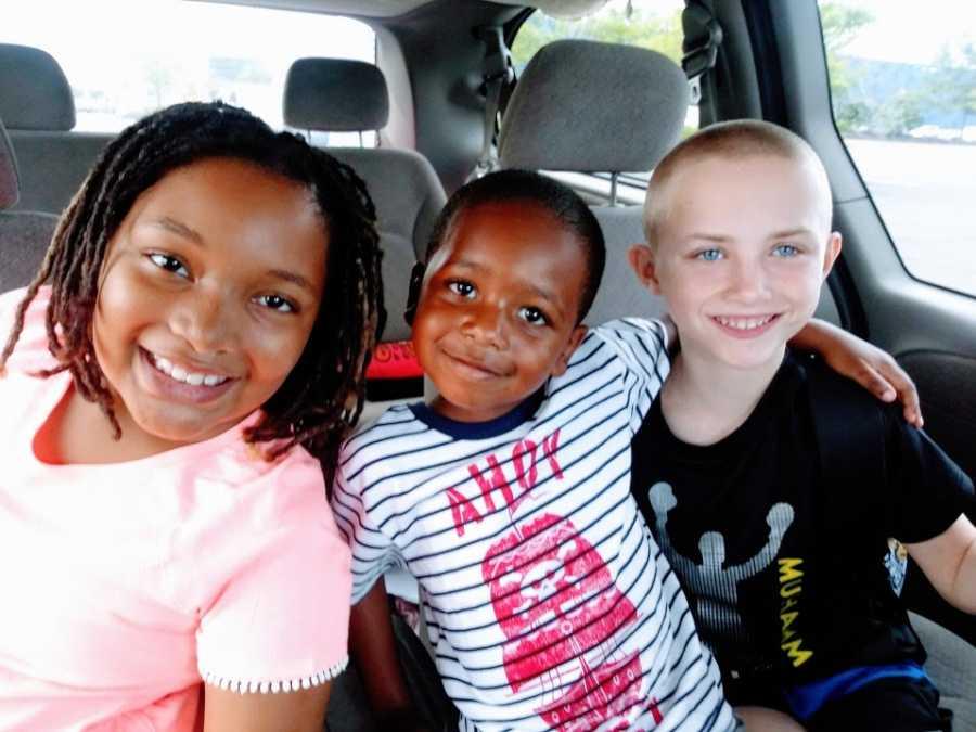 Three siblings sit in the back of their parents' van