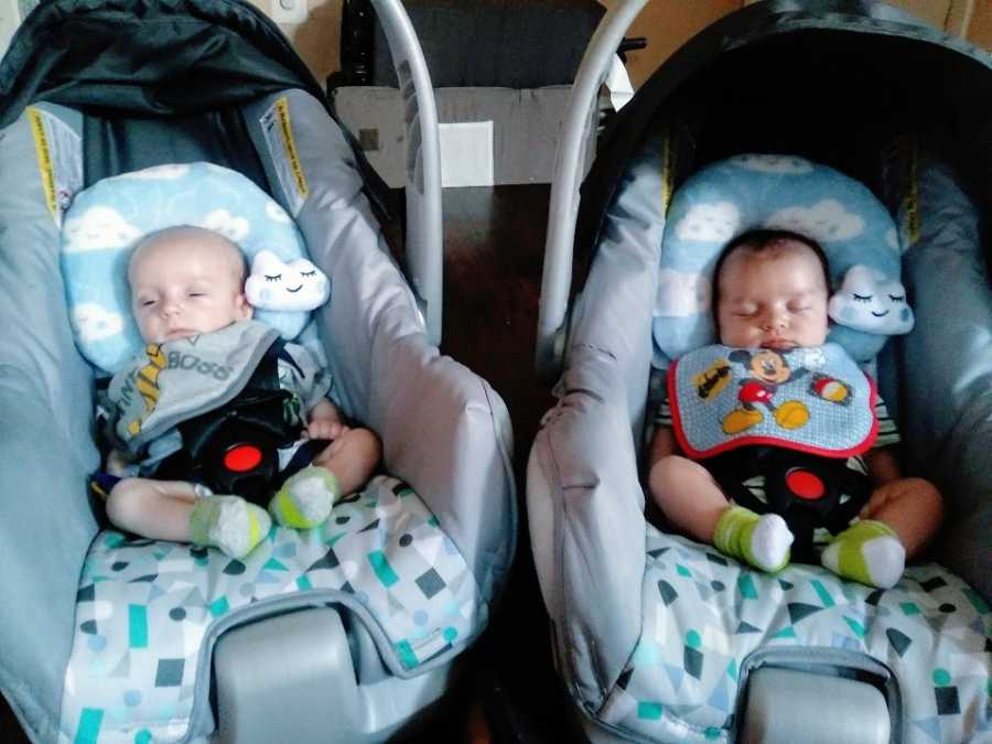 Twin boys sit in matching carseats