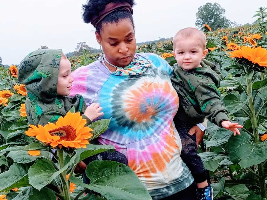 A mother holds her twin sons walking through a field of sunflowers