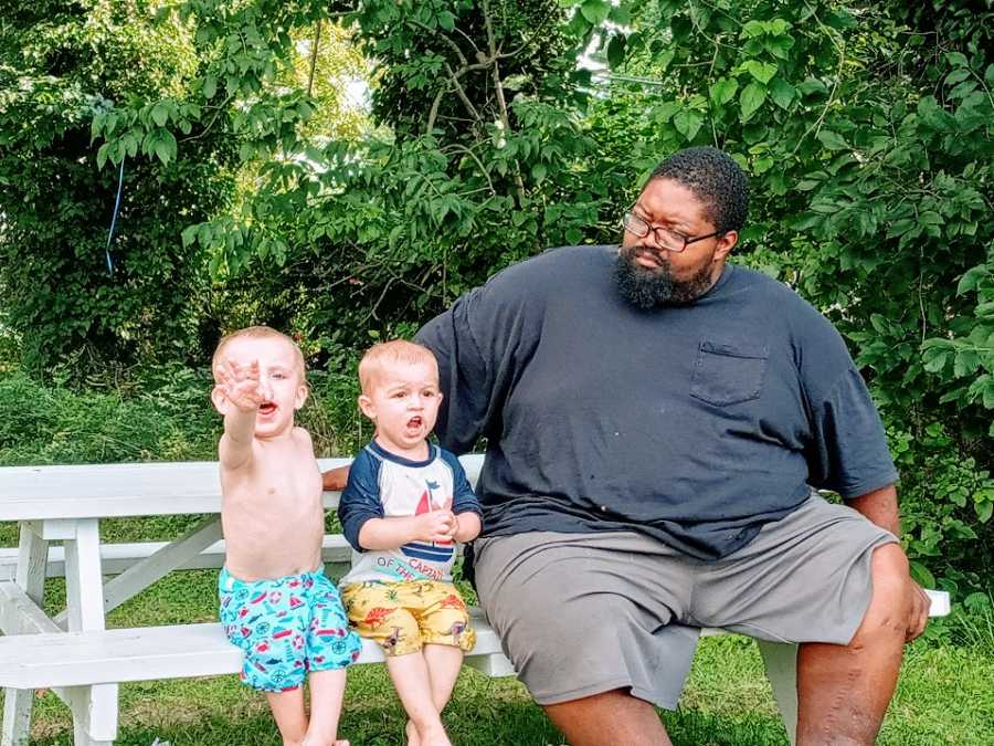 A father sits on a bench with his twin sons