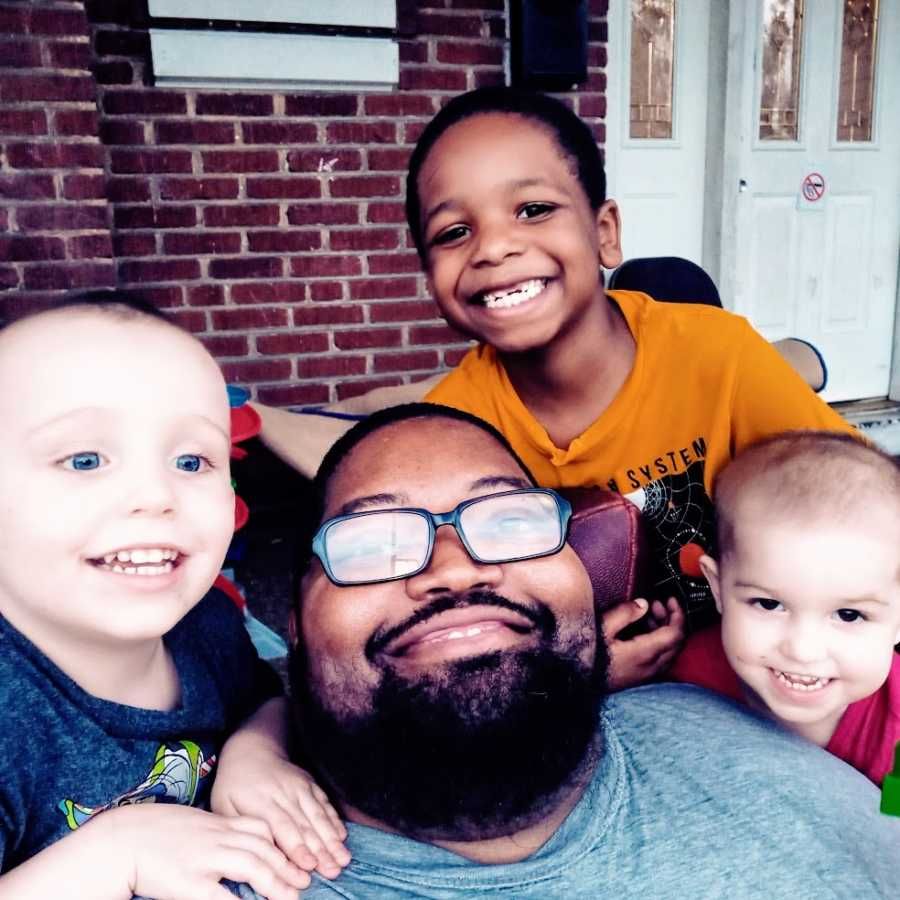 A father sits with his three sons on the front porch
