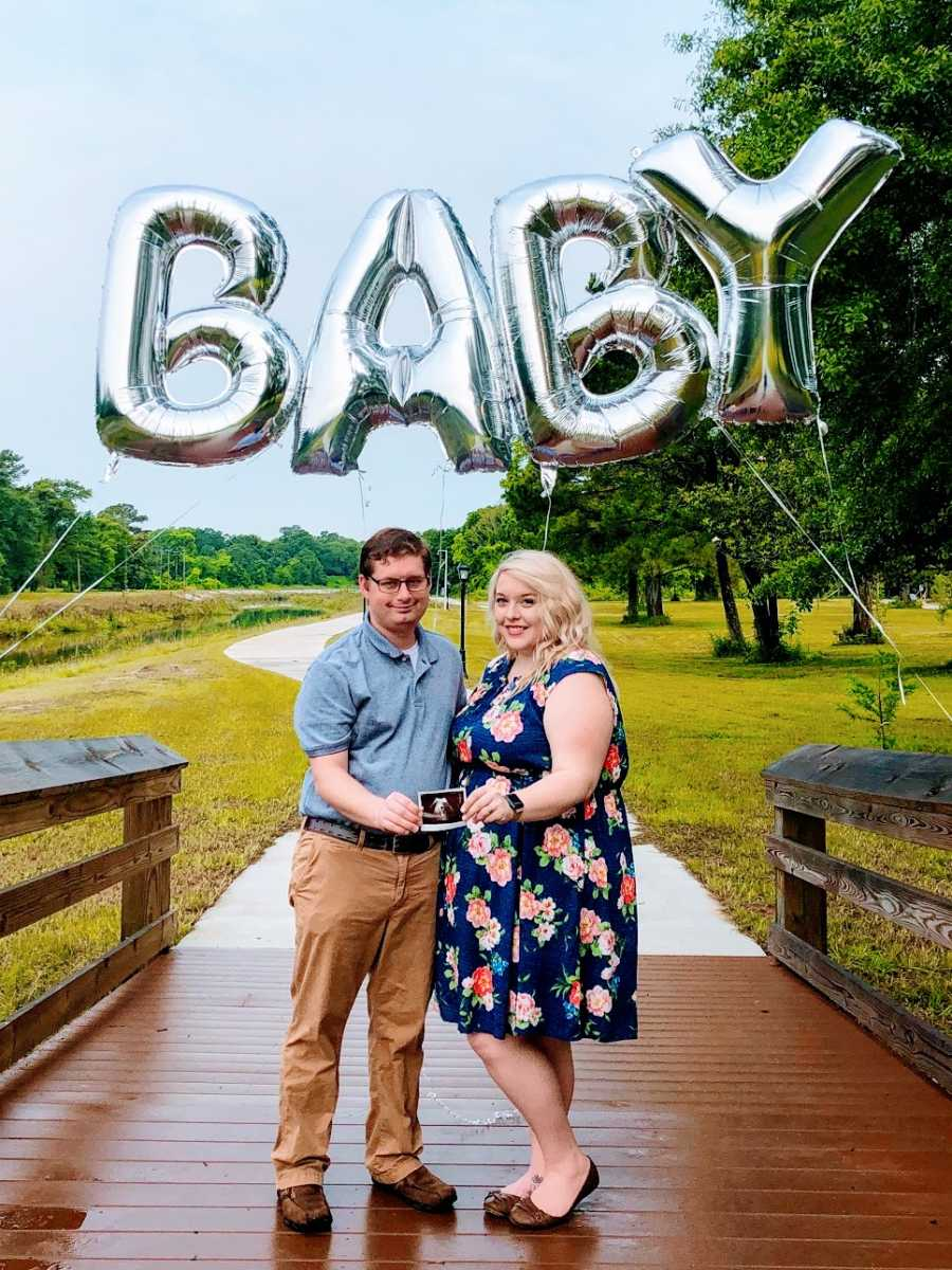 A woman and her husband stand under balloons spelling BABY
