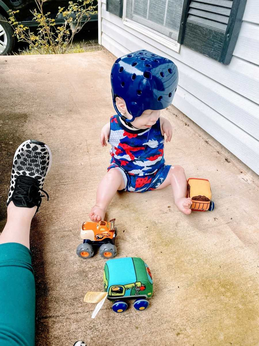 A little boy with no arms wearing a helmet and playing with trucks