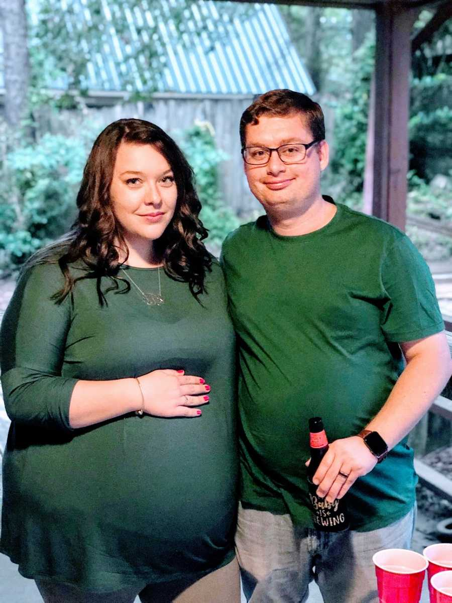 A pregnant woman and her husband wearing green shirts