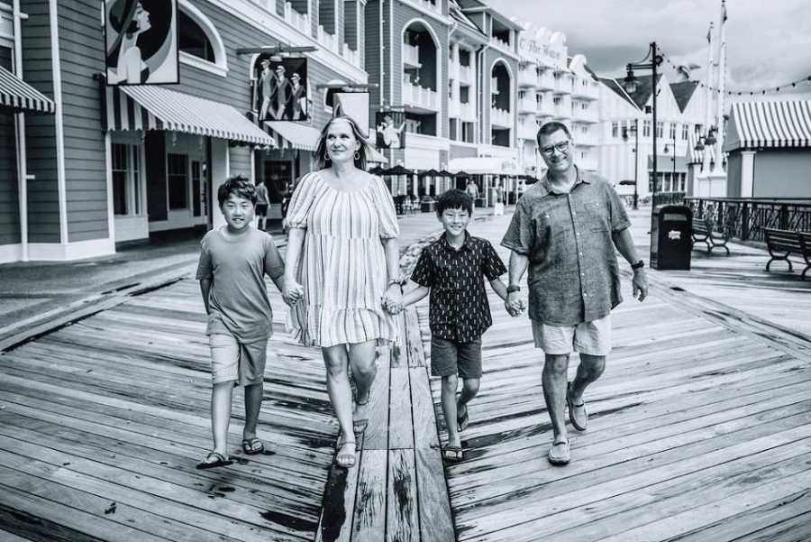 一个家庭,他们的两个儿子在木板走道上