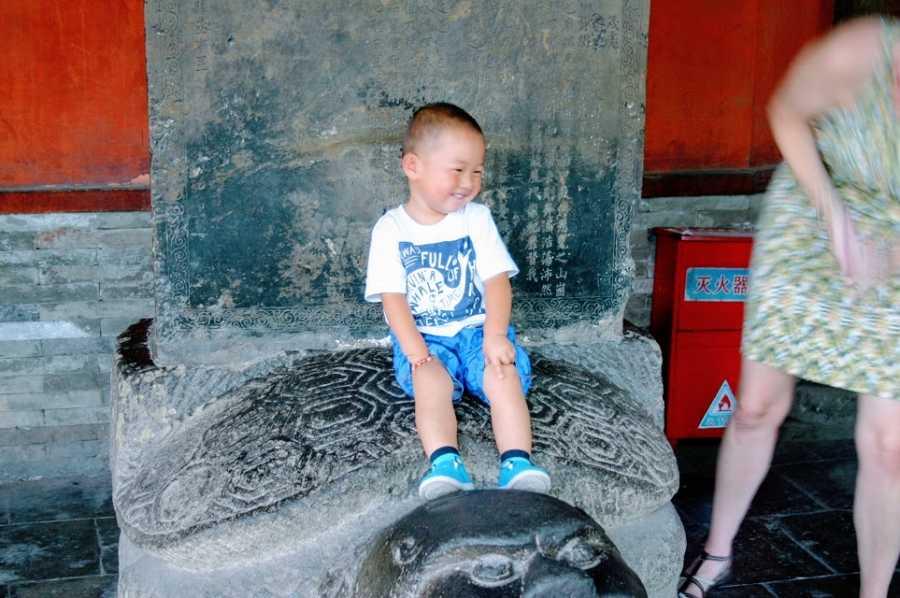 一个小男孩坐在一座石头建筑的顶部