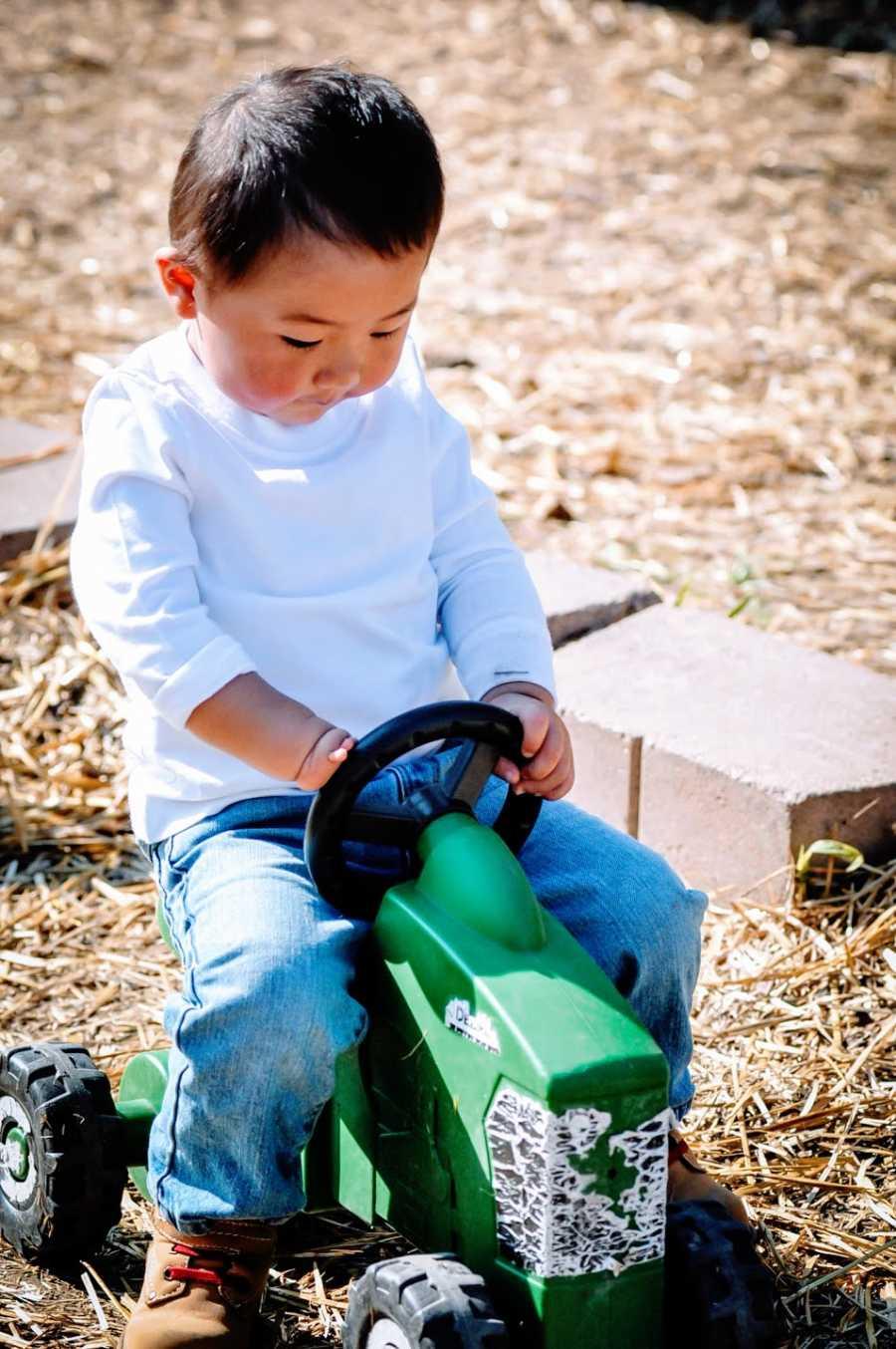 一个小男孩坐在玩具拖拉机上