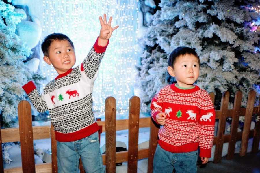 一对男孩站在一起穿着圣诞毛衣