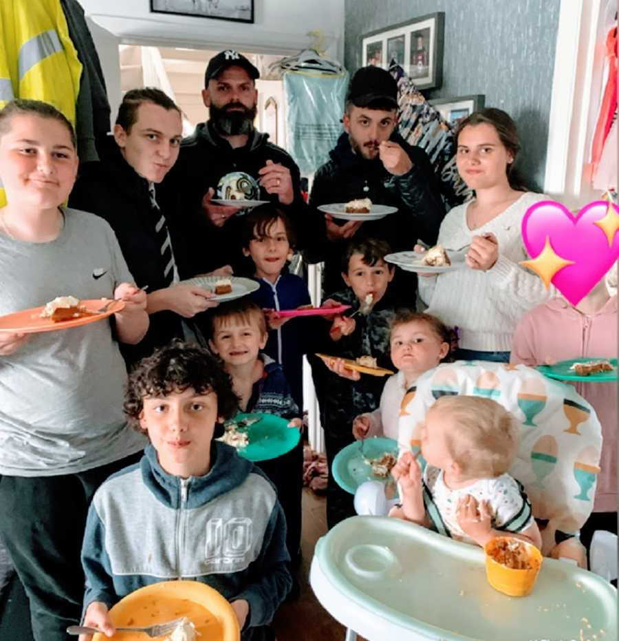 A family with eleven kids stands in the kitchen