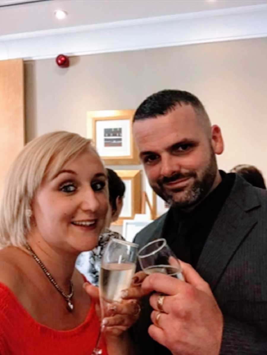 A husband and wife holding wine glasses