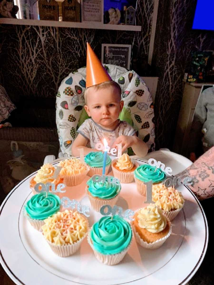 A little boy wearing a birthday hat sits in front of cupcakes