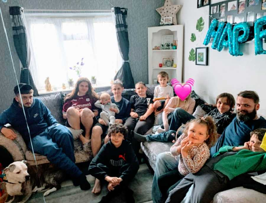 A family with eleven kids sits on a sofa