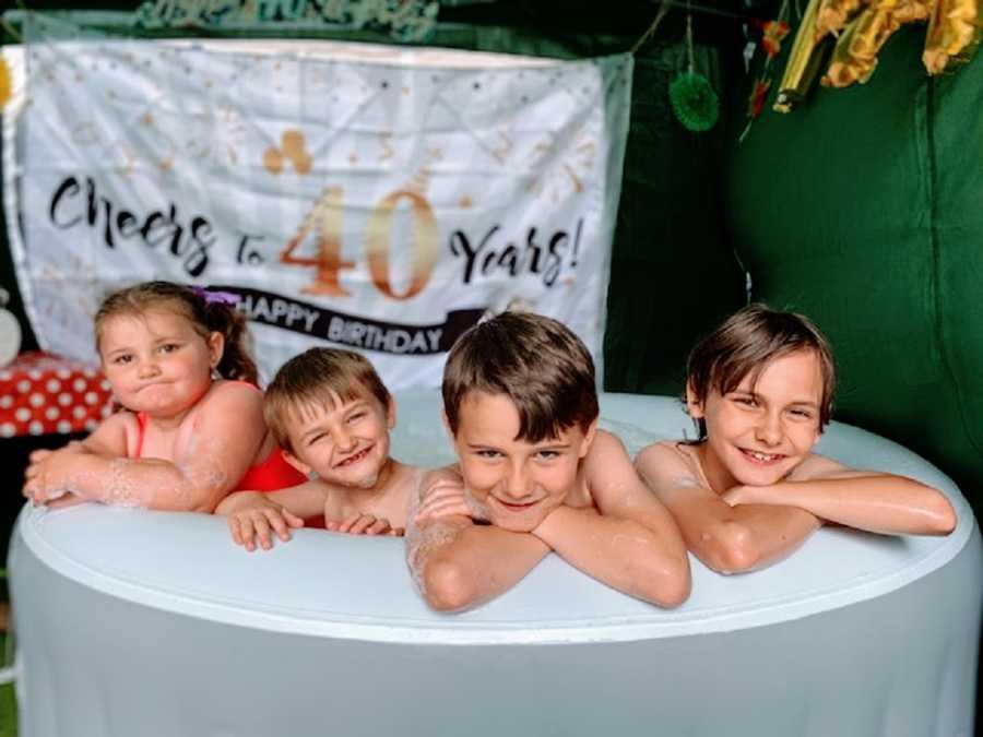 Four children sit in a bathtub