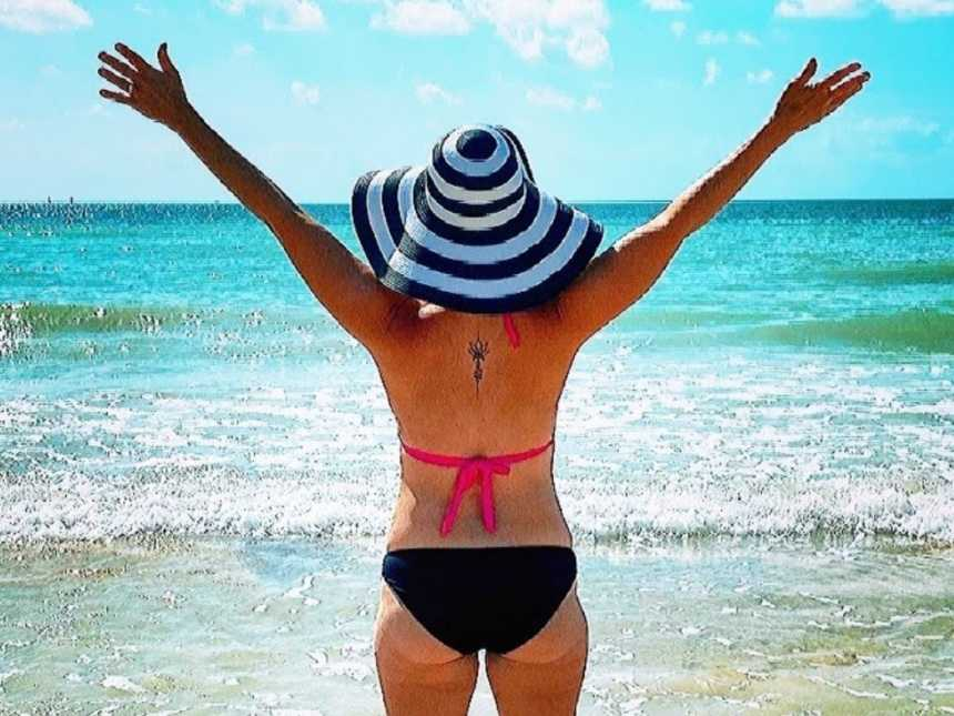 A woman stands by the beach with her arms outstretched