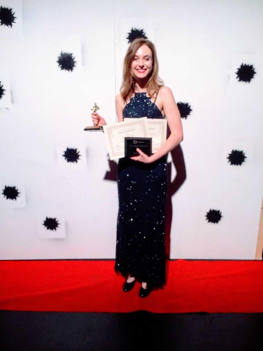 A woman wearing a black dress holds up an award