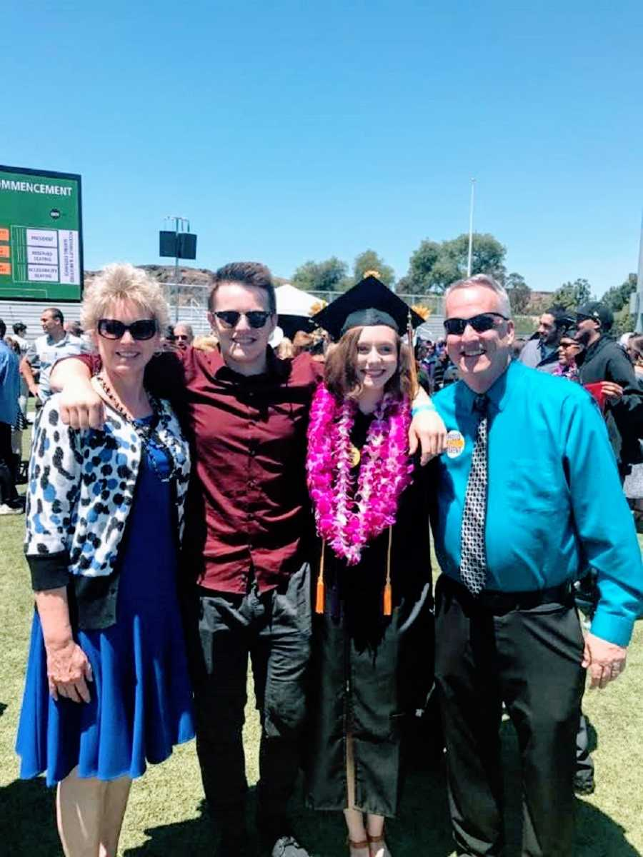 A young woman wearing a cap and gown stands with her family
