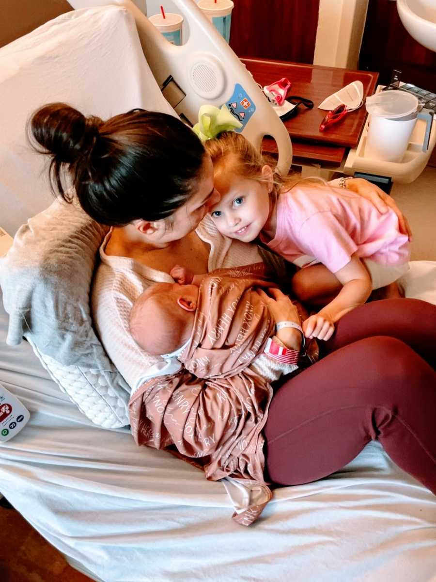 A mother sits in a hospital bed with her newborn and her daughter