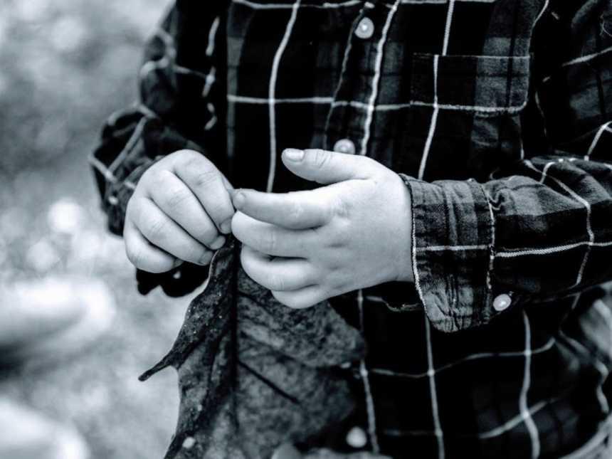 A boy wearing a plaid shirt picks at his fingernails