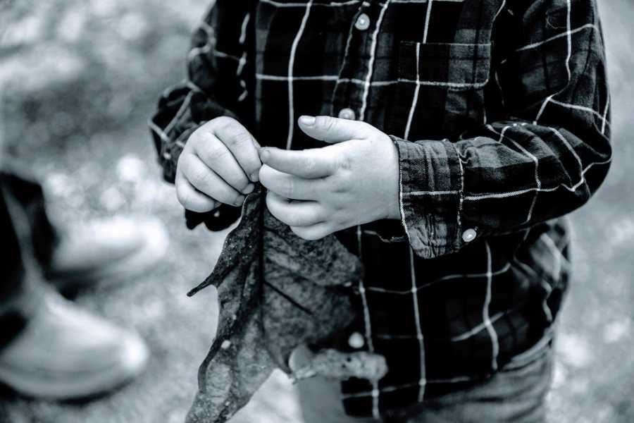 A foster child wearing a plaid shirt picks at his fingernails