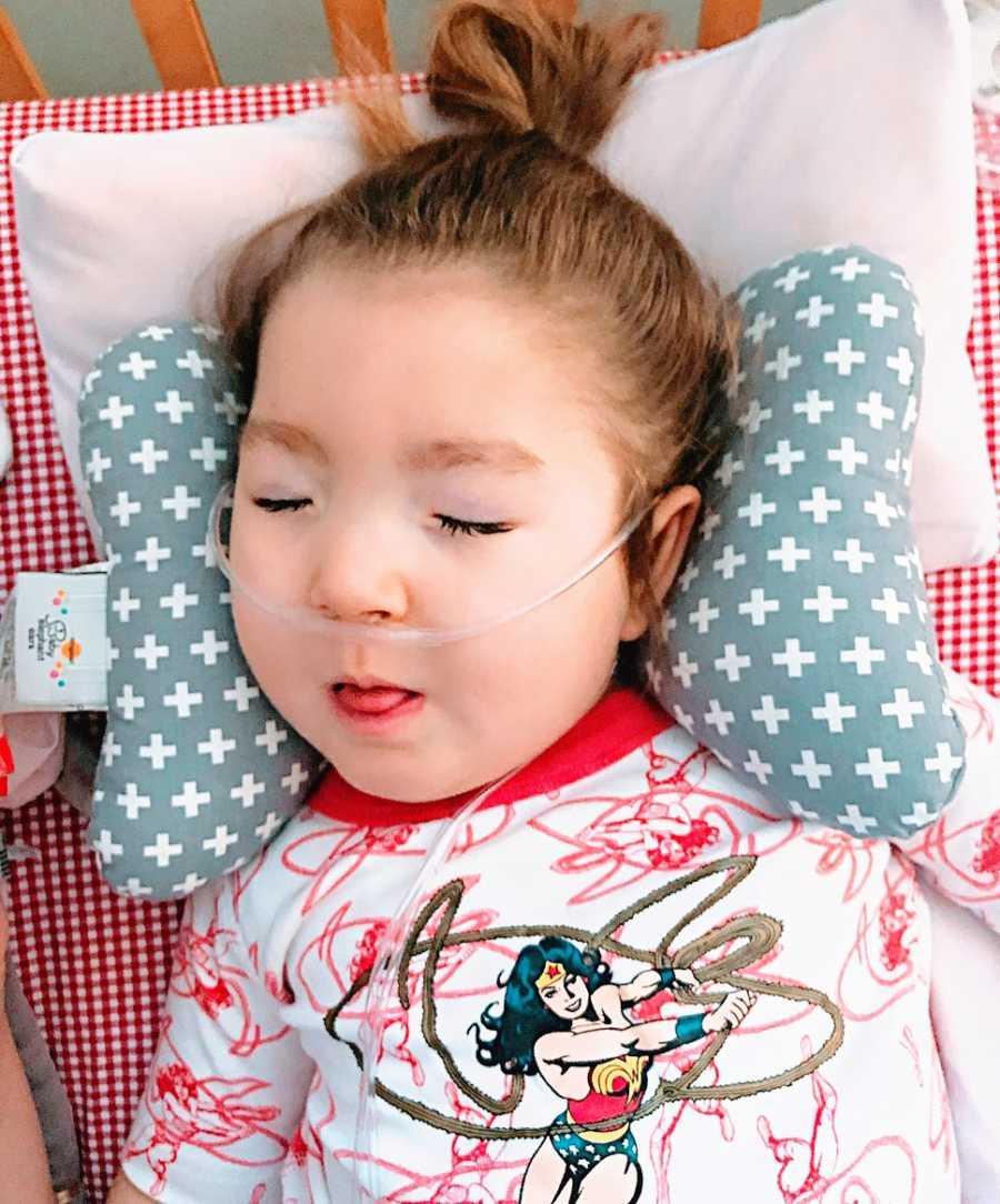 A little girl with epilepsy lies on a pillow wearing an oxygen tube