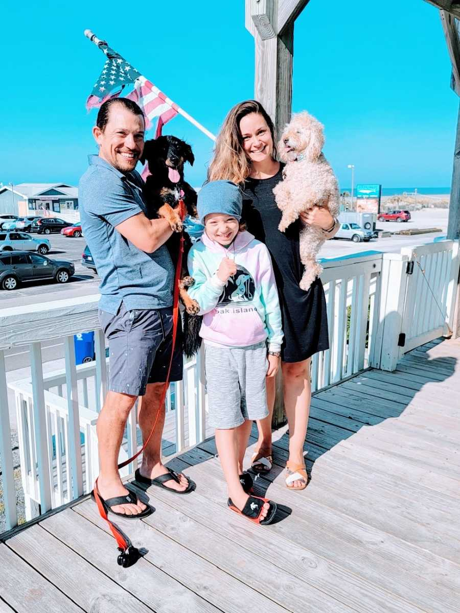 A couple stand with their dogs and their son on their front porch