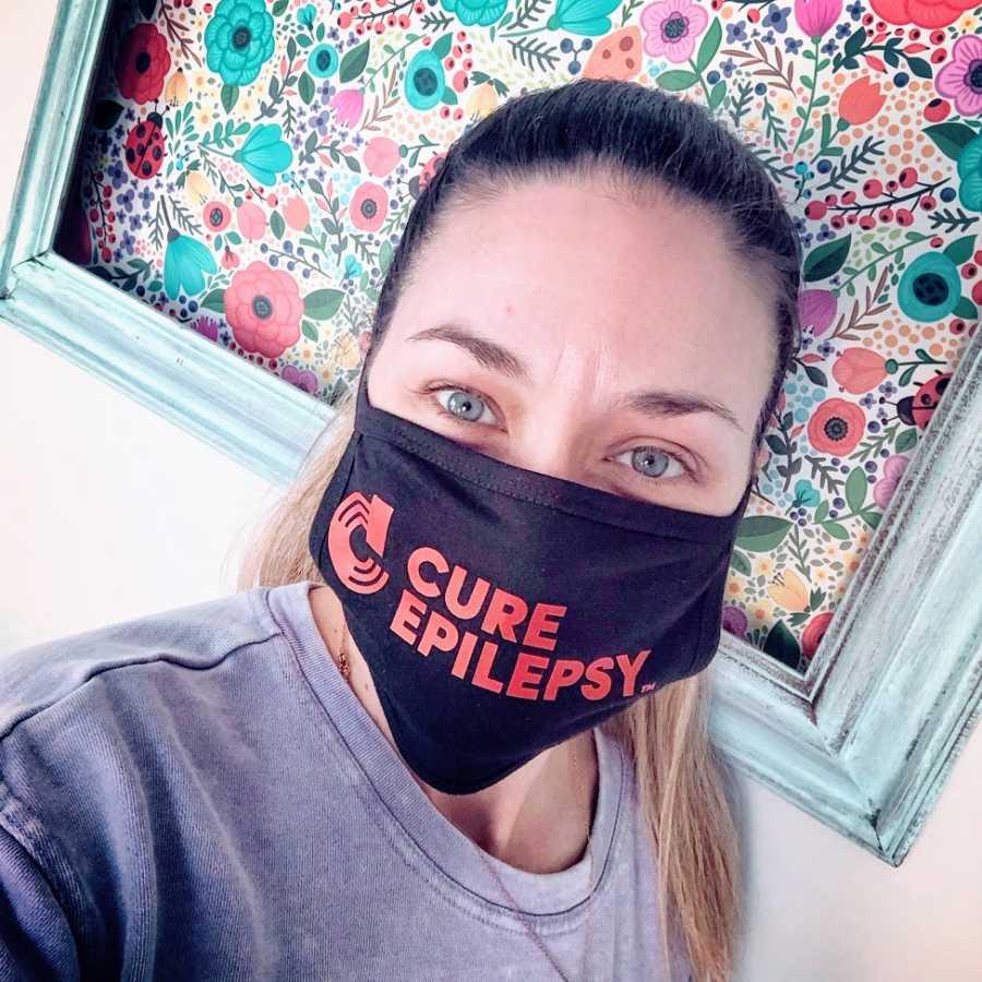 A woman wears a CURE Epilepsy mask