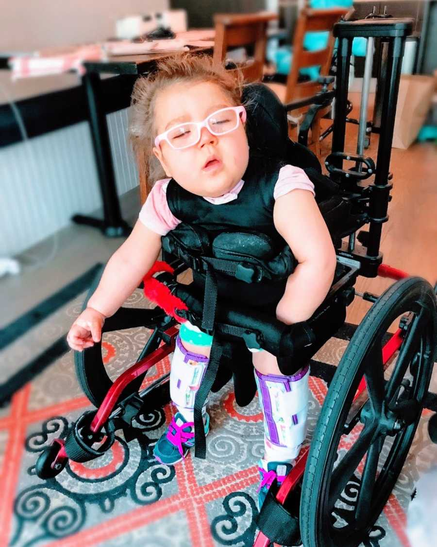 A little girl with epilepsy stands in a wheelchair