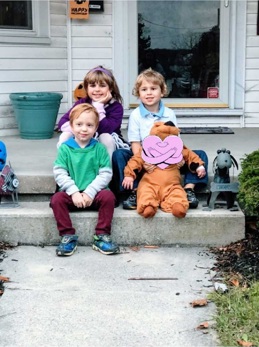 Three children sit on steps with their foster brother