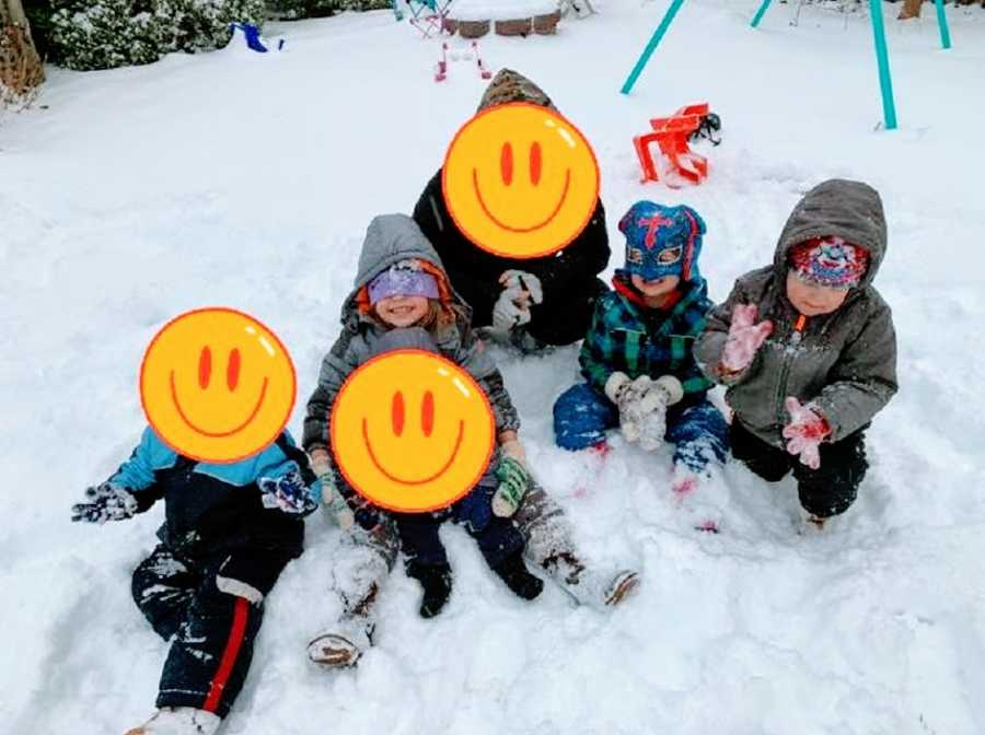 A group of children play with each other in the snow