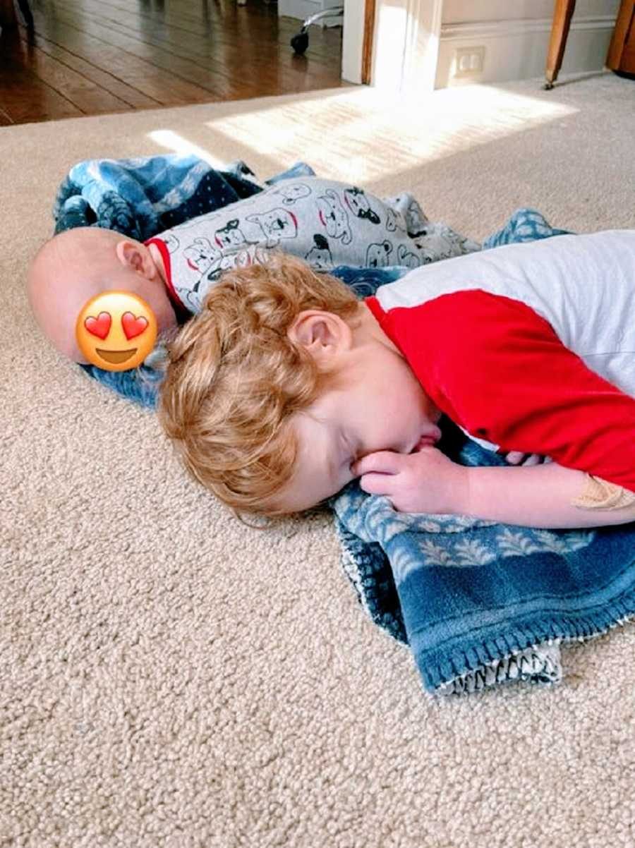 A toddler sleeps next to a foster baby