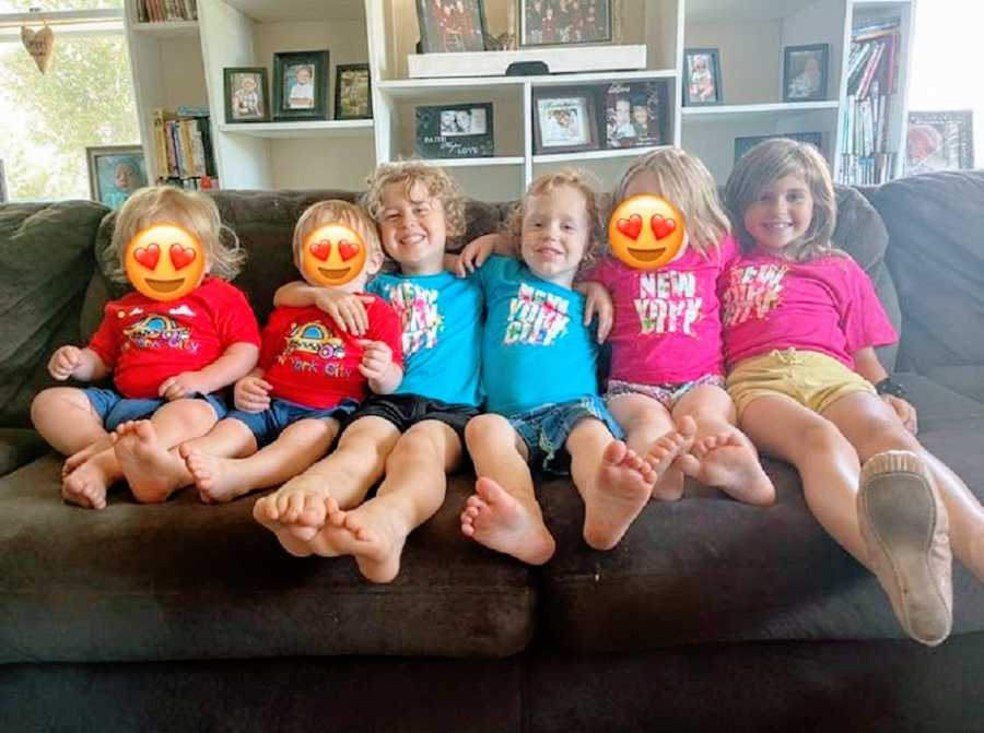 Six children sit together on a couch in matching T-shirts