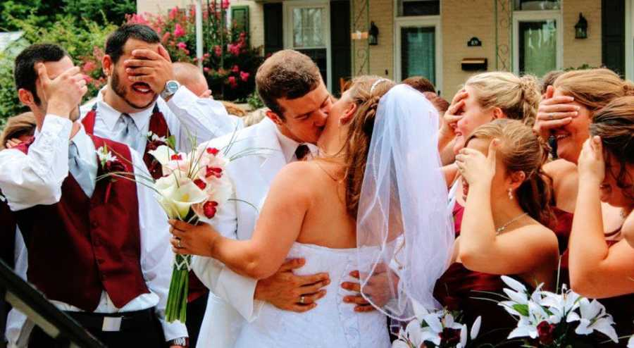 A groom kisses a bride while onlookers cover their eyes
