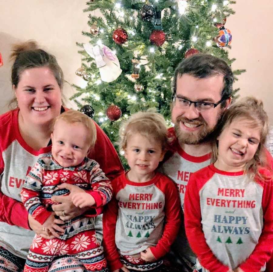 Parents with their 3 children dressed in matching holiday pajamas