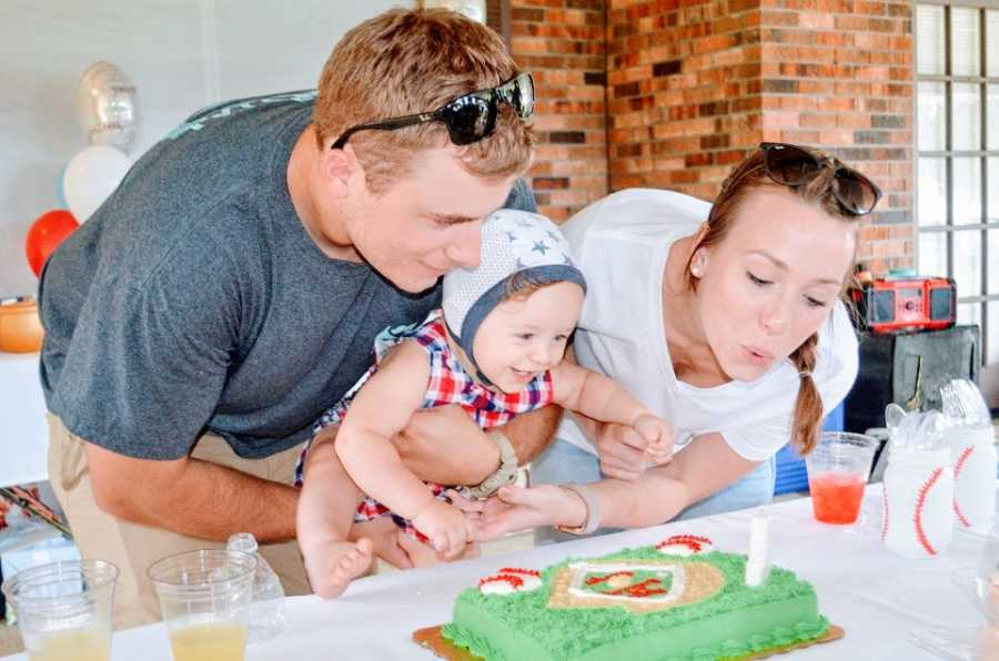 A little boy and his parents blowing out birthday candles