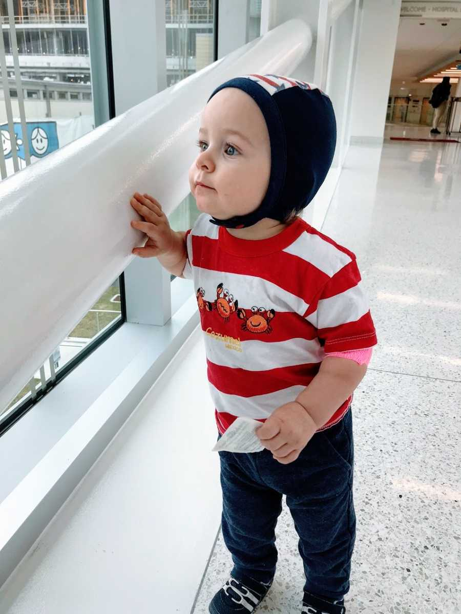 A little boy wearing a cap and a red striped shirt looks out a window