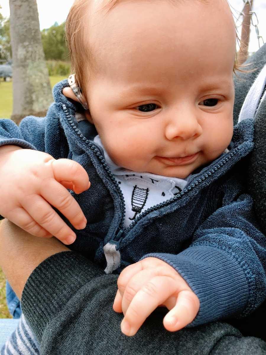 A little boy wearing hearing aids and a sweatshirt