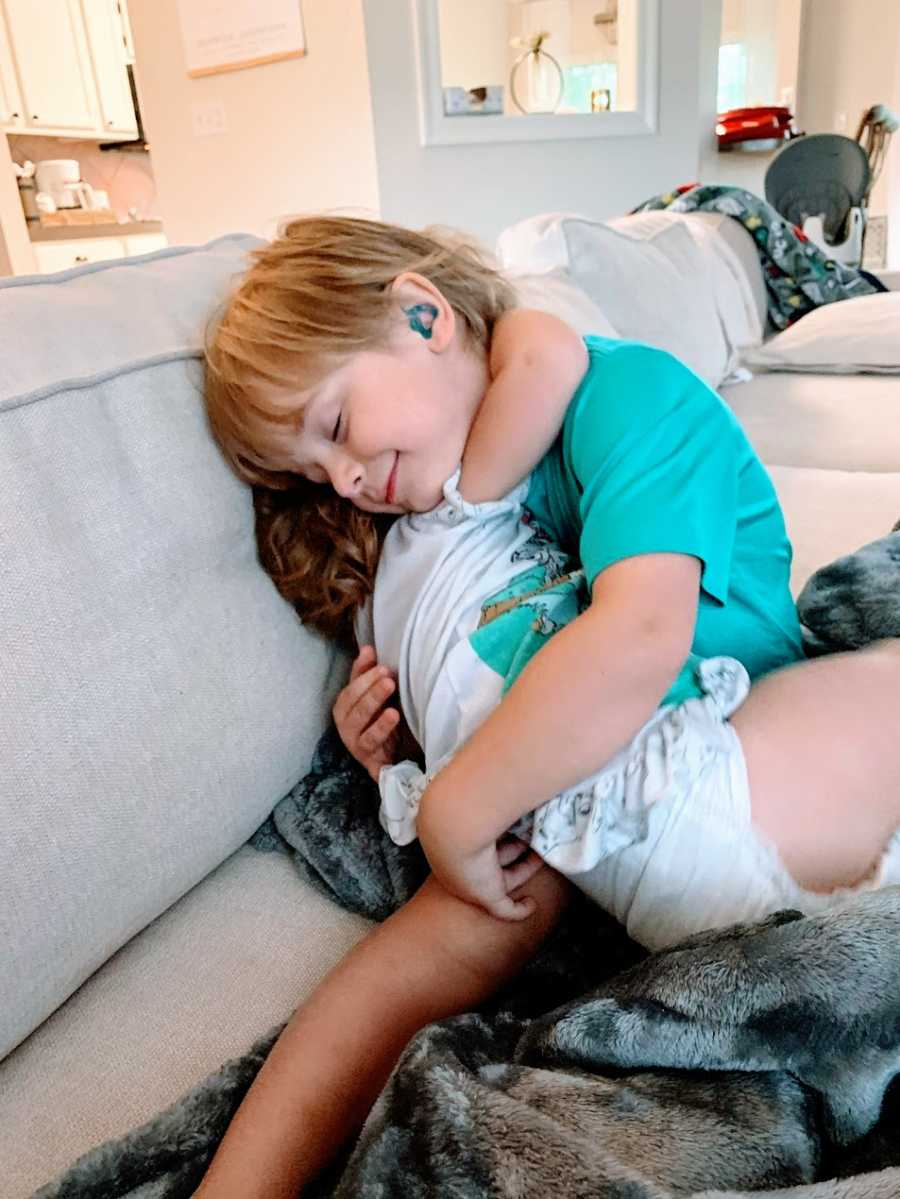 A little boy with hearing aids hugs his little sister