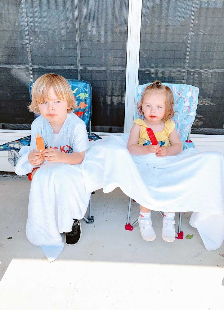 A boy and his sister sit in chairs holding popsicles